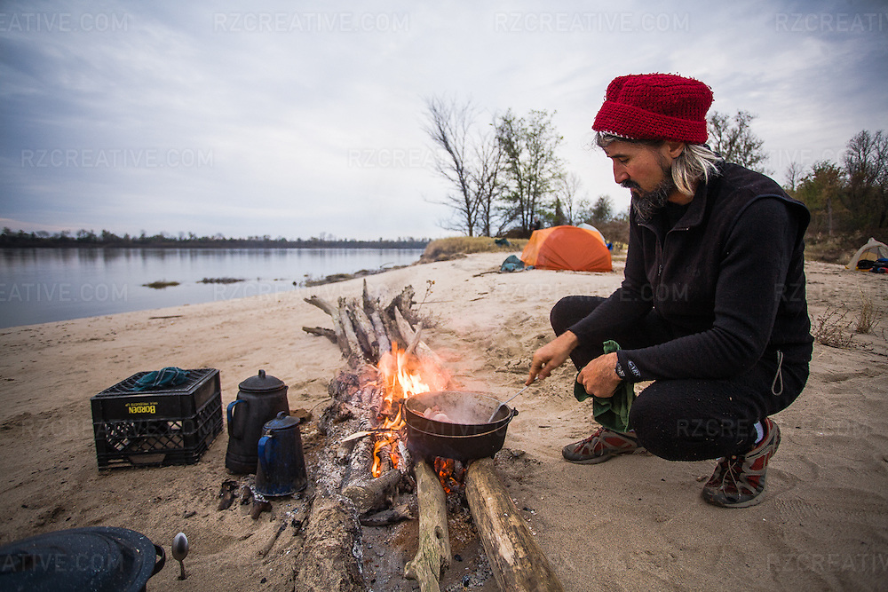 John Ruskey of Clarksdale, Mississippi based Quapaw Canoe Company cooks breakfast over a driftwood fire on a remote sandy beach on the lower Mississippi River Delta.