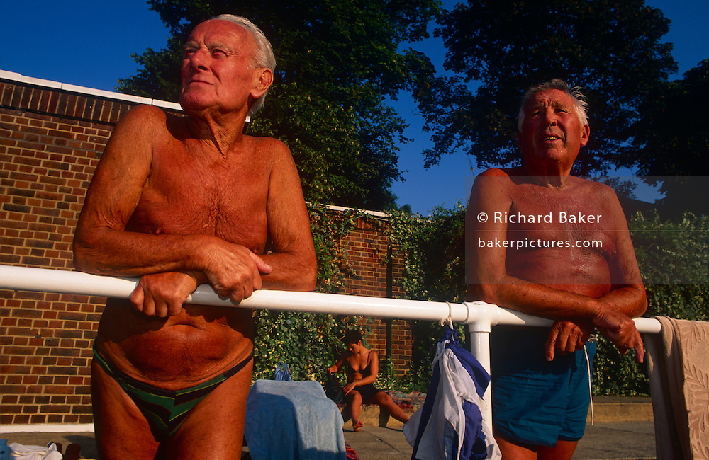 Two old friends regularly spend afternoons sunbathing at Brixton Lido and talk of old times in the sun. The friends gather every morning in the summer at Brockwell (Brixton) Lido. This is a favourite place in the capital for varied groups of people  to meet, swim or just hang out like these London taxi drivers who regularly meet for exercise sessions, accumulating sun tans during long periods in the sunshine. Brockwell Lido in Herne Hill SE24 was originally built in 1937 at a time of coastal and city pool-building but went into decline when bathers preferred to holiday in warmer Spain. Its revival happened when local entrepreneurs re-opened the business and it now enjoys a reputation for some of the best urban swims in the UK.