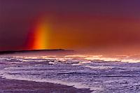 Rainbow behind crashing waves at Strandfontein (near Cape Town), South Africa