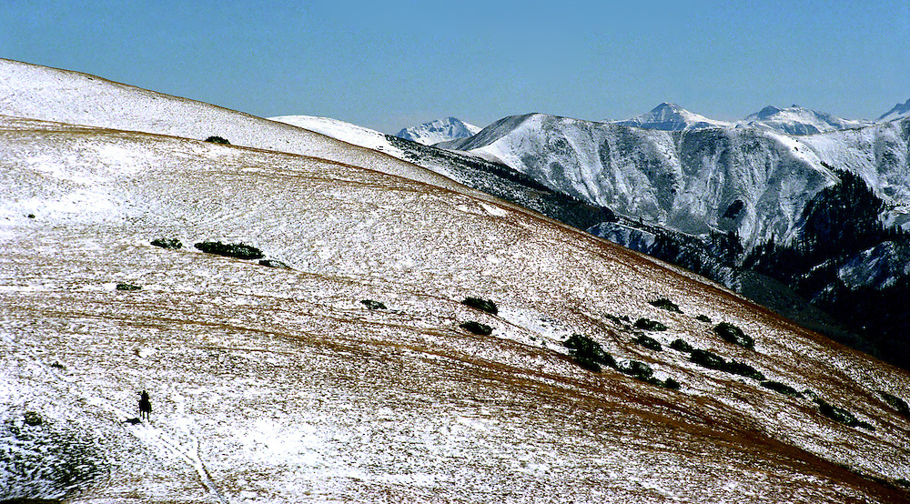 A hunter rides a horse above timberline during a hunt in the Colorado Rocky Mountain wilderness