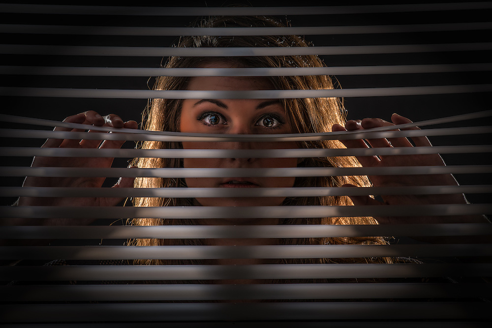 Beautiful girl mysteriously peeking through the blinds