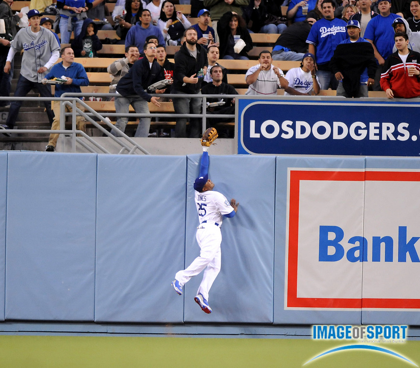 May 6, 2008; Los Angeles, CA, USA; Los Angeles Dodgers center fielder Andruw Jones (25) leaps unsuccessfully at the outfield wall to catch a first-inning home run by Ryan Chuch of the New York Mets (not pictured) at Dodger Stadium.