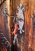 Keys swing in a keyhole on a door lock. Visit the farm museum of Rygnestadtunet (at Nordigard, in Nørdre Rygnestad, near Valle, Setesdal, Aust-Agder, Norway) to admire a unique 1590 three-story storehouse, a farmhouse with open-hearth room dating from before the Black Death (1349-50), and 15th century painted textiles.