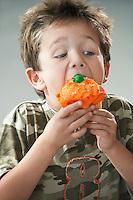 Young boy eating cupcake