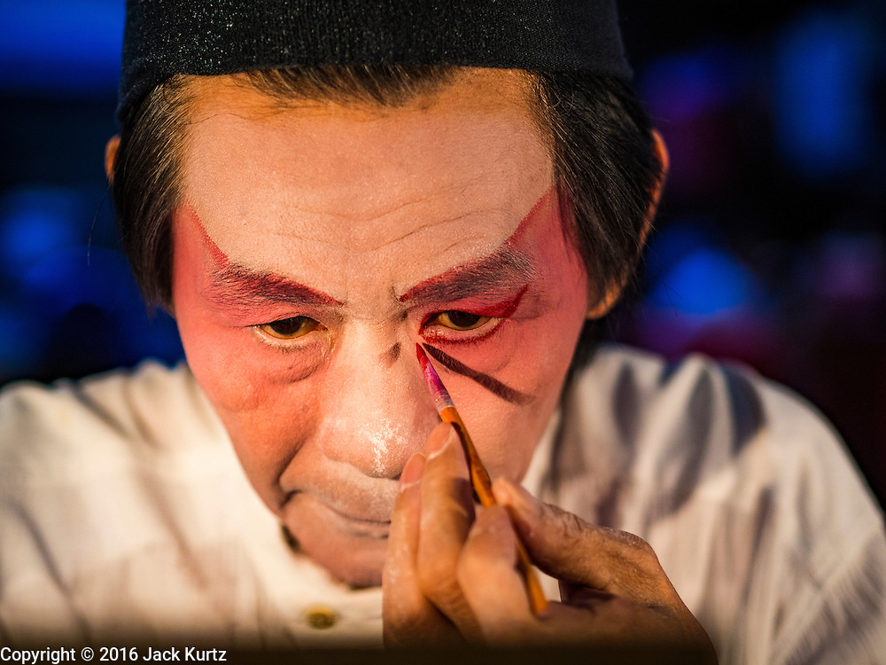 "30 JUNE 2016 - BANGKOK, THAILAND: A performer puts on his eye makeup before a Chinese opera performance at Chiao Eng Piao Shrine in Bangkok. Chinese opera was once very popular in Thailand, where it is called ""Ngiew."" It is usually performed in the Teochew language. Millions of Chinese emigrated to Thailand (then Siam) in the 18th and 19th centuries and brought their culture with them. Recently the popularity of ngiew has faded as people turn to performances of opera on DVD or movies. There are about 30 Chinese opera troupes left in Bangkok and its environs. They are especially busy during Chinese New Year and Chinese holidays when they travel from Chinese temple to Chinese temple performing on stages they put up in streets near the temple, sometimes sleeping on hammocks they sling under their stage.       PHOTO BY JACK KURTZ"