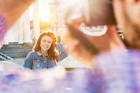 Portrait of young beautiful woman posing while being photograph by his boyfriend with lens flare in background