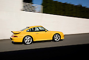 Image of yellow coupe in blurred motion on road, 1997 Porsche 911, 993 Turbo S in Washington, Pacific Northwest