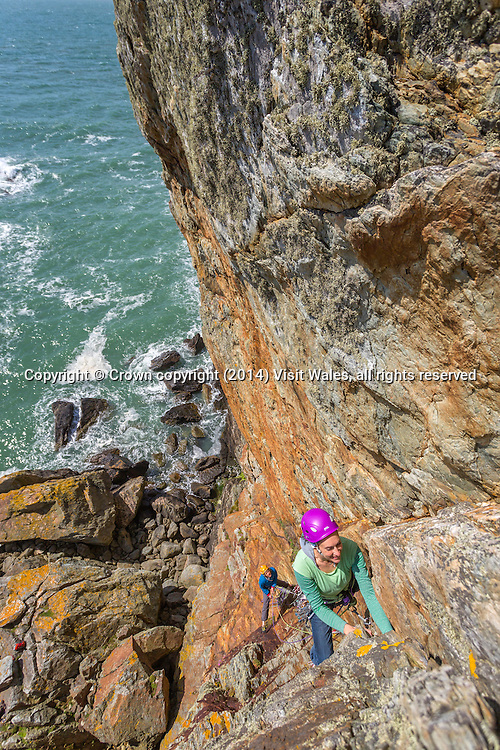 View down from top of cliff to two female climbers ascending<br /> Rock Climbing<br /> Rhoscolyn<br /> Holy Island<br /> Anglesey<br /> North<br /> Adventure<br /> Activities and Sports