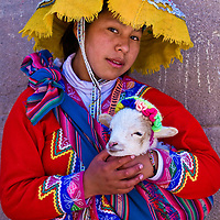 "CUSCO , PERU - MAY 27 : Unidentified Peruvian girl in traditional colorful clothes holding a lamb in here arms in the "" Unesco world heritage"" city ""Cusco"" on May 27 2011"