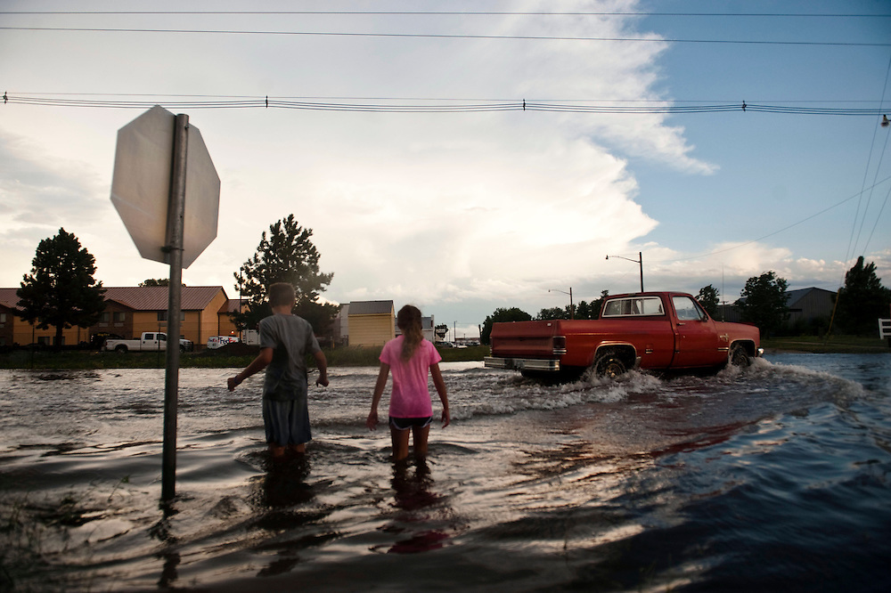 Clay Crouse, 11, left, and Avery Crouse, 9, stand knee deep in water at the corner of 2nd and Cherry Street in Valentine July 30, 2013 after a rainfall. (Photo by Lauren Justice)