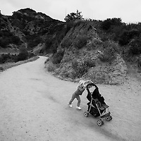 A girl pushes an empty stroller along a hiking trail May 14, 2011, on Mount Lee in Los Angeles.