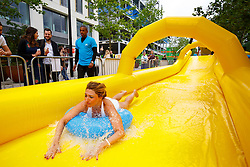 © Licensed to London News Pictures. 19/06/2015. London, UK. People sliding down a 100 metre-long inflatable waterslide towards Battle Bridge Place in King's Cross, London on Friday, June 19, 2015 at Lipton Ice Tea hosts 'Rise & Slide' event. Photo credit: Tolga Akmen/LNP