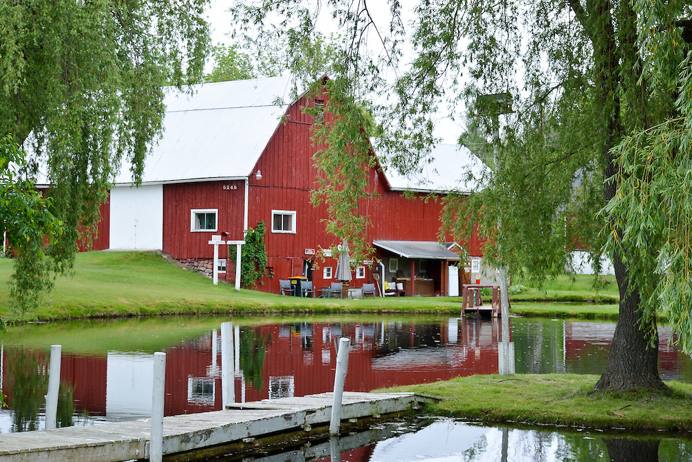 A Stark Red Farmhouse Reflects Off Of A Still Pond In Jordan River Valley, East Jordan Michigan