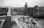 A statue on top of the GPO gets a good look at the decapitated Nelson's Pillar, blown up by a republican bomb in the early hours of the morning. A well-known landmark and meeting place, the Pillar also offered a great view over the city, and its 168 steps could be climbed for a fee of sixpence (adults)..08.03.1966