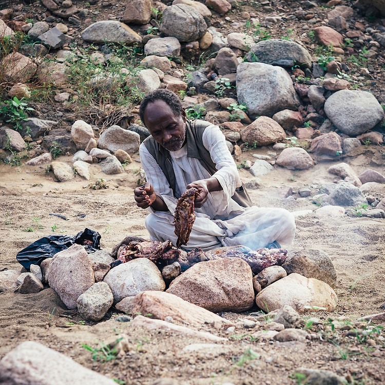 A Bishari bedouin cooking a small lamb for dinner.