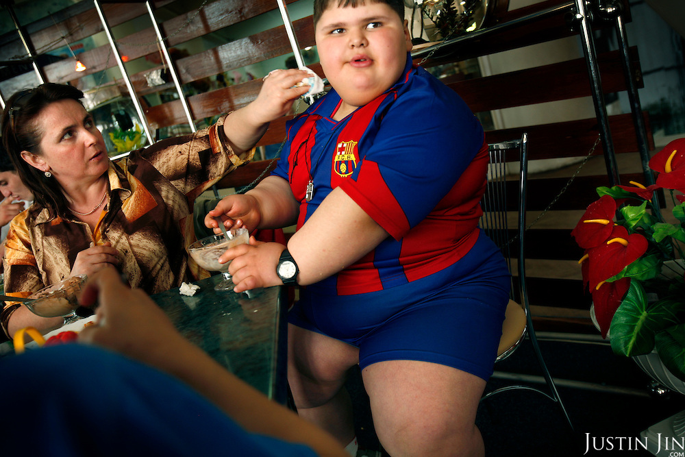 Dzhambulat Khotokhov, 6, one of the fattest boys in the world, eats his fourth ice cream in Nal'chik, near in his home town Terek, in southern Russia. His mother wipes his mouth. .Now 1.4 metres tall and weighing about 100 kg, Khotokhov has grabbed world attention as the biggest kid in the world since he was three. .Khotokhov lives with his mother Neyla and his brother, 14-year-old Mukha. .