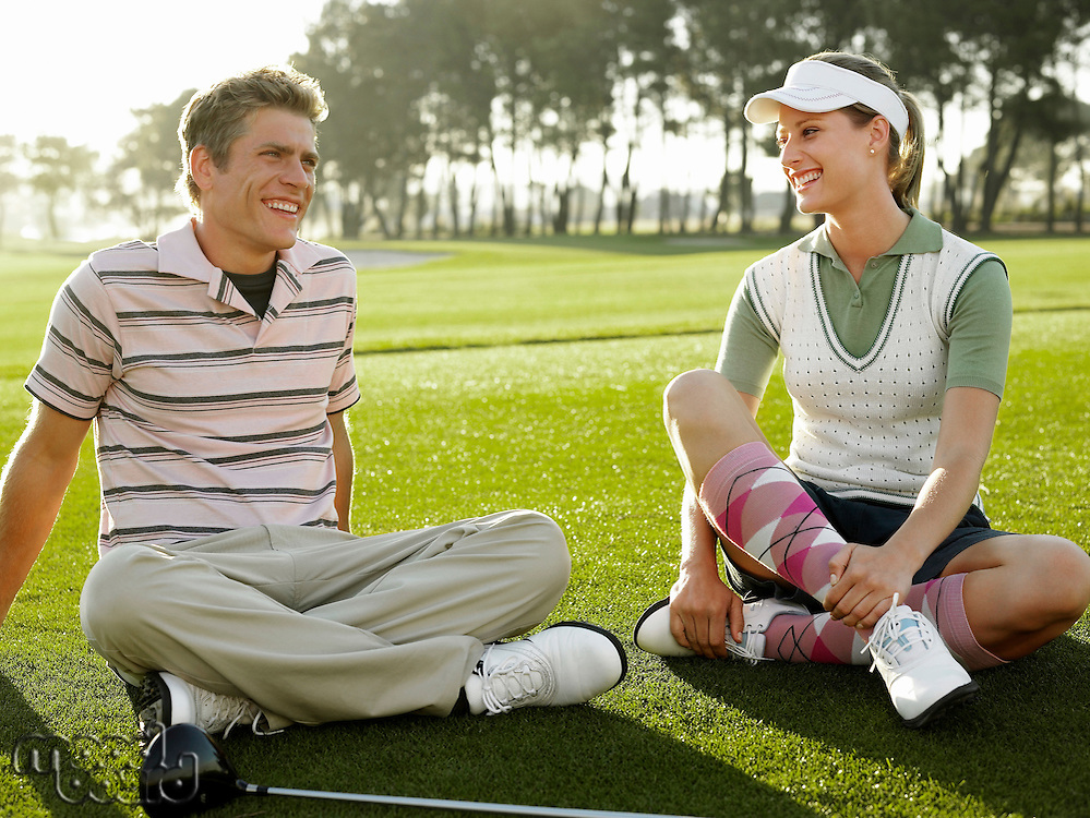 Two young golfers sitting on court smiling