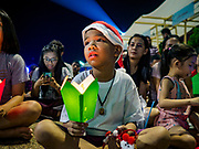 """23 DECEMBER 2018 - CHANTABURI, THAILAND: A boy holds a candle while carolers perform at the Cathedral of the Immaculate Conception's Christmas Fair in Chantaburi. Cathedral of the Immaculate Conception is holding its annual Christmas festival, this year called """"Sweet Christmas @ Chantaburi 2018"""". The Cathedral is the largest Catholic church in Thailand and was founded more than 300 years ago by Vietnamese Catholics who settled in Thailand, then Siam.  PHOTO BY JACK KURTZ"""