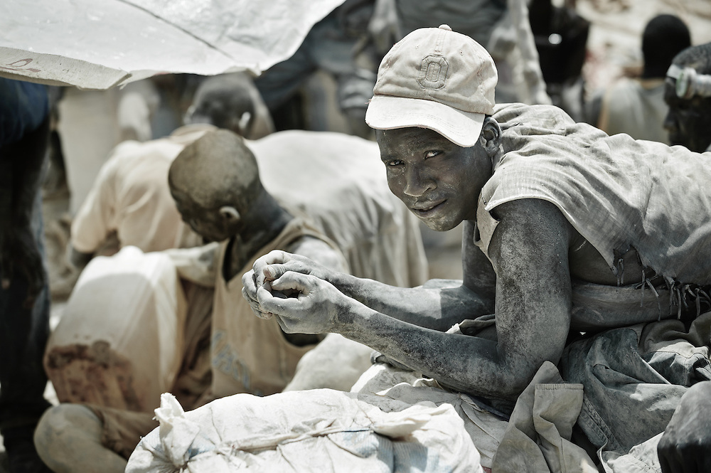 Stock photograph of  African gold miners in Burkina Faso, exhausted and covered in mud from a day down the shaft digging for ore.