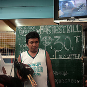 THE PHILIPPINES (Manila). 2009. Owners wait to prepare their birds for fighting at the cockfighting at the La Loma Cockpit, La Loma, Manila. Photo Tim Clayton <br /> <br /> Cockfighting, or Sabong as it is know in the Philippines is big business, a multi billion dollar industry, overshadowing Basketball as the number one sport in the country. It is estimated over 5 million Roosters will fight in the smalltime pits and full-blown arenas in a calendar year. TV stations are devoted to the sport where fights can be seen every night of the week while The Philippine economy benefits by more than $1 billion a year from breeding farms employment, selling feed and drugs and of course betting on the fights...As one of the worlds oldest spectator sports dating back 6000 years in Persia (now Iran) and first mentioned in fourth century Greek Texts. It is still practiced in many countries today, particularly in south and Central America and parts of Asia. Cockfighting is now illegal in the USA after Louisiana becoming the final state to outlaw cockfighting in August this year. This has led to an influx of American breeders into the Philippines with these breeders supplying most of the best fighting cocks, with prices for quality blood lines selling from PHP 8000 pesos (US $160) to as high as PHP 120,000 Pesos (US $2400)..