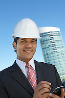 Businessman in hardhat using PDA outdoors, portrait