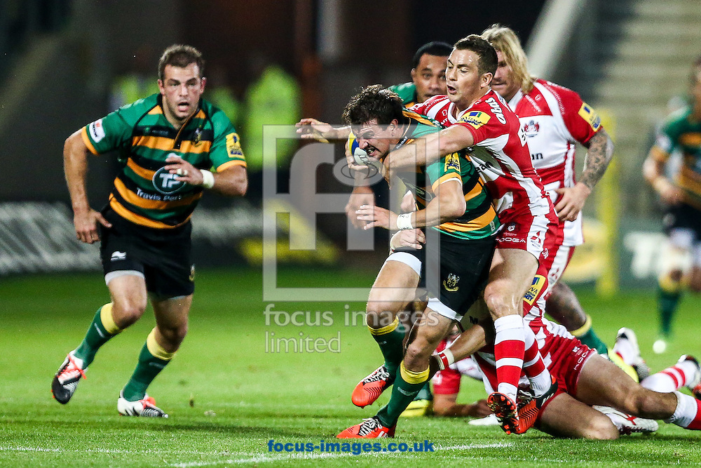 Lee Dickson of Northampton Saints (centre) is tackled by  Greg Laidlaw of Gloucester Rugby (right)  during the Aviva Premiership match at Franklin's Gardens, Northampton<br /> Picture by Andy Kearns/Focus Images Ltd 0781 864 4264<br /> 05/09/2014