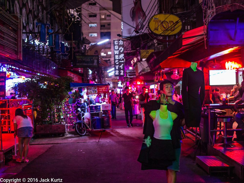 "03 NOVEMBER 2016 - BANGKOK, THAILAND: A street vendor selling mourning clothes for women working on ""Soi Cowboy,"" one of Bangkok's best known ""adult entertainment districts."" Bangkok's infamous nightlife has been scaled back during the mourning period for the late Bhumibol Adulyadej, King of Thailand. The revered King died on 13 October 2016 at age 88. The government declared a year of mourning. The government ordered Thailand's notorious adult entertainment districts to turn off their neon lights, dress employees in black and ensure that music can't be heard on the street in front of the venues for 30 days, the government said the entertainment venues could resume normal operations on 14 November.        PHOTO BY JACK KURTZ"