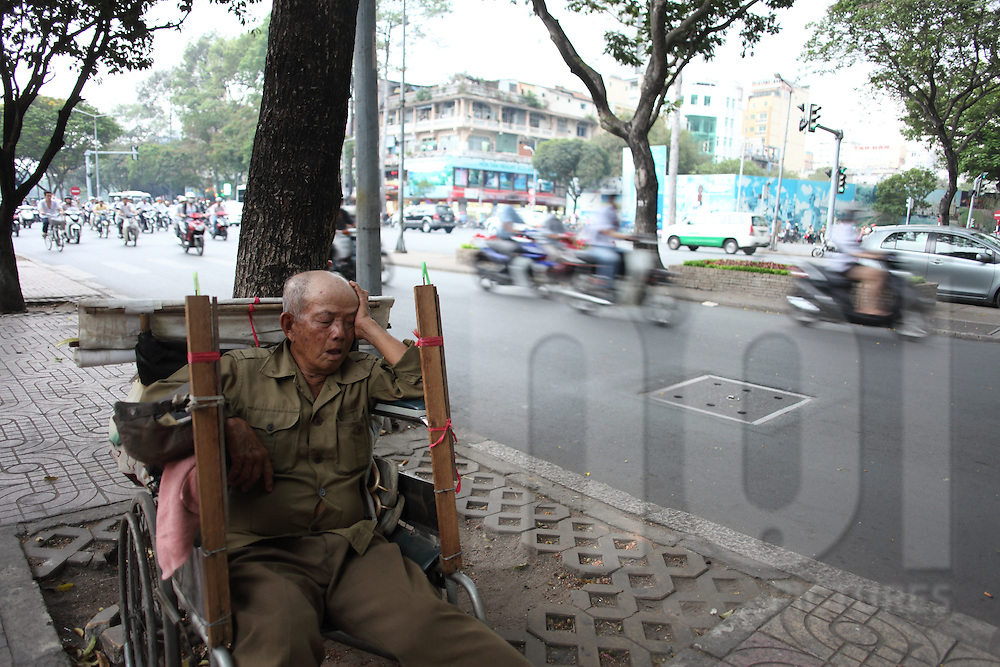 Elderly Vietnamese man sleeping in a wheelchair on the noisy road side in District 1, Ho Chi Minh City, Vietnam, Southeast Asia