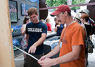 Jess Lovetinsky (from left) of Iowa CIty talks with artist Andy Van Schyndle of Green Bay, Wisconsin about one of his paintings at his booth at Iowa Arts Festival in Iowa City on Saturday, June 5, 2010. This is Van Schyndle 5th year as a vendor at the Festival and says out of the 24 shows he does a year this is his favorite. Over 125 artists had booths at the event which runs through Sunday. Other activities include live music, children's activities, and food booths.