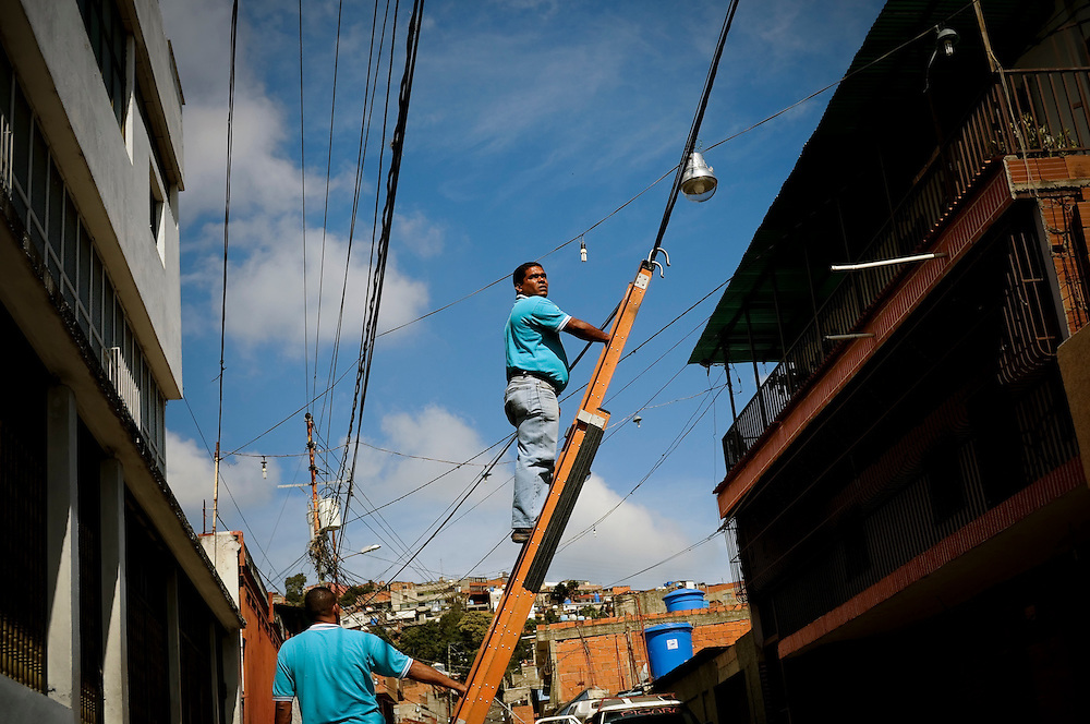 Government maintenance workers fix power lines in the El Junquito slum in Caracas, Venezuela. People living in Venezuelan slums are faced daily with inadequate municipal services, including water and electricity shortages, poor roads and an unreliable waste management system.