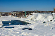Frozen Niagara falls - the American Falls with Rainbow Bridge in background, from the Canadian side.