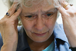 Older woman; upset; and holding her head in her hands,