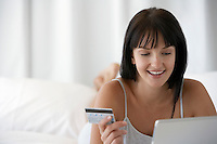 Young woman lying on bed holding credit card whilst using laptop portrait