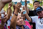 "01 FEBRUARY 2014 - BANGKOK, THAILAND: Thai voters hold up their national ID cards during a march to a polling place to try to vote. The voters were turned back by police who blocked access to the polls because armed anti-government protestors would not allow voters to cast their ballots. Thais went to the polls in a ""snap election"" Sunday called in December after Prime Minister Yingluck Shinawatra dissolved the parliament in the face of large anti-government protests in Bangkok. The anti-government opposition, led by the People's Democratic Reform Committee (PDRC), called for a boycott of the election and threatened to disrupt voting. Many polling places in Bangkok were closed by protestors who blocked access to the polls or distribution of ballots. The result of the election are likely to be contested in the Thai Constitutional Court and may be invalidated because there won't be quorum in the Thai parliament.    PHOTO BY JACK KURTZ"
