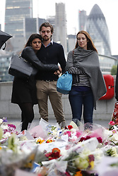 © Licensed to London News Pictures. 05/06/2017. London, UK.        Members of the public hold a vigil at Potters Fields Park outside City Hall in London for those who lost their lives in the London Bridge terror attack.  Three men attacked members of the public  after a white van rammed pedestrians on London Bridge. Ten people including the three suspected attackers were killed and 48 injured in the attack. Photo credit: Tolga Akmen/LNP
