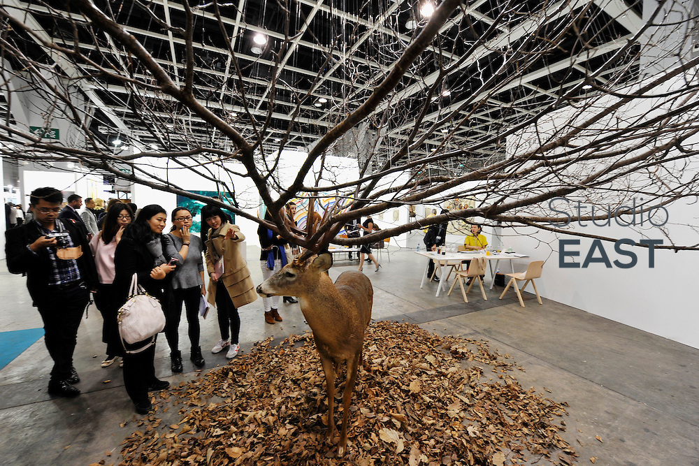 HONG KONG - MARCH 13:  Visitors look at sculpture 'Untitled' by Kim Myeongbeom made of deer taxidermy, leaves and branches on the preview day of Art Basel on March 13, 2015 in Hong Kong, Hong Kong.  (Photo by Lucas Schifres/Getty Images)