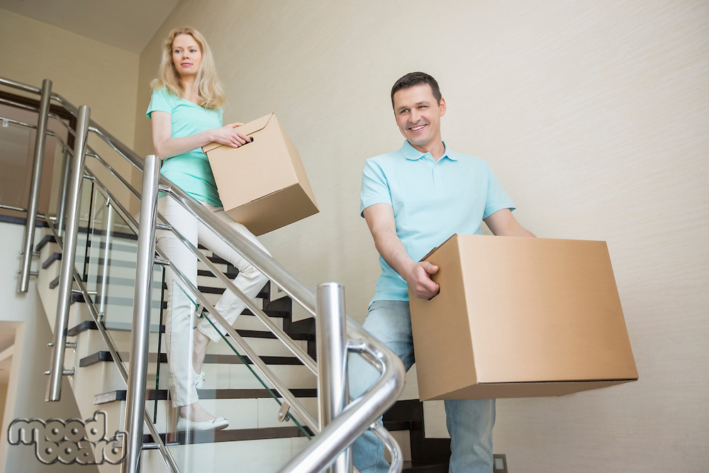 Couple carrying cardboard boxes while moving down steps at new home