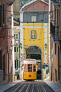 Funicular - Elevador da Bica, carrying local people and tourists on tram tracks on steep hill in City of Lisbon, Portugal