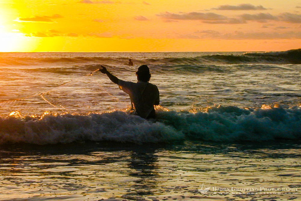 Bali, Badung, Kuta. Kuta Beach just before sunset. A fisherman tries his luck.