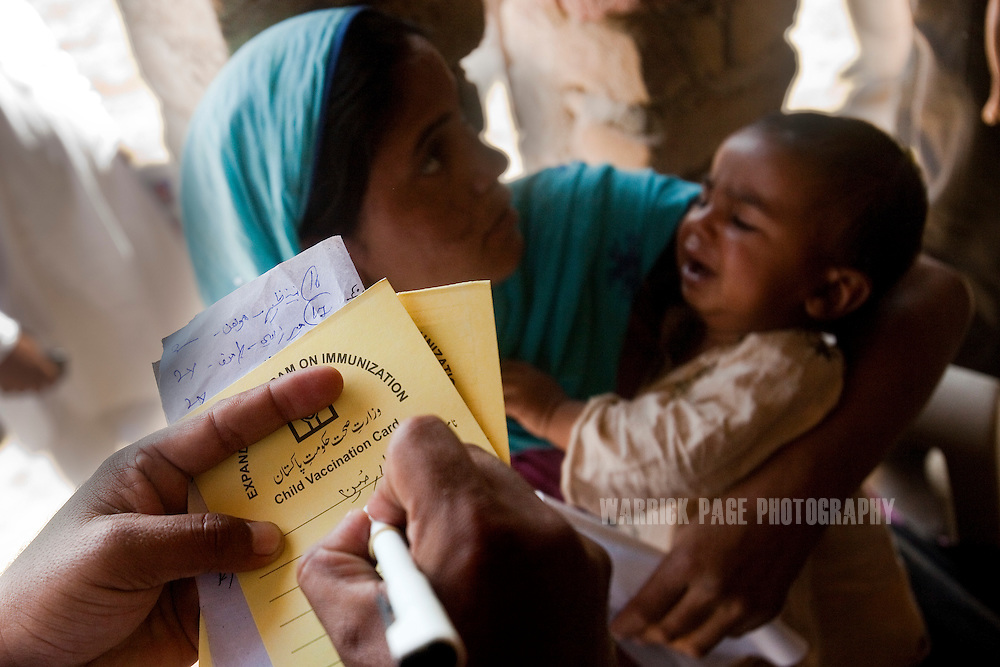 A WHO-sponsored NGO worker fills out an immunization form after giving an injection to a baby in a rural village, 16 March, 2011, outside Naushero Feroz, Pakistan. According to UN reports, hundreds of thousands of children in Pakistan suffer from severe-acute-malnutrition, with 15.1% of children experiencing acute malnutrition. Child malnutrition has breached emergency levels in Pakistan's Sindh province, after monsoon floods devastated the country's poorest region for a second year. Extreme poverty, poor diet and health, exposure to disease, and inadequate sanitation and hygiene annually produce alarming levels of malnutrition amongst children, but the floods have increasingly endangered an already vulnerable population. (Photo by Warrick Page)
