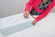 Midsection of girl writing on birthday gift at table in house