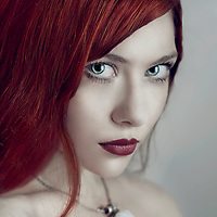 Close up of a young woman with red hair wearing only a necklace glancing at the camera.