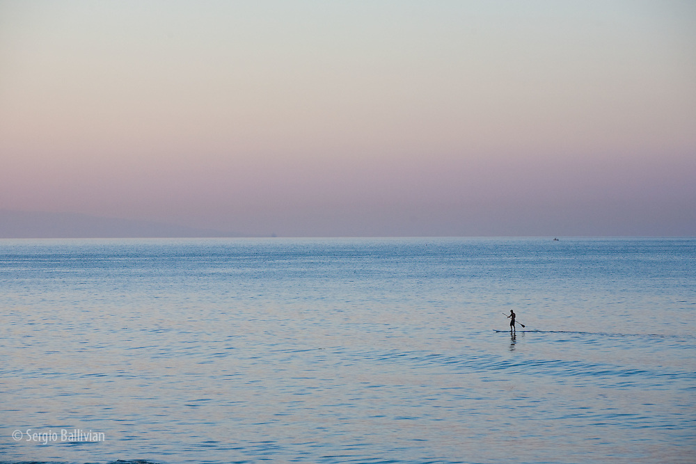 A lone man paddleboards along the Pacific Ocean near a beach in Los Angeles, CA
