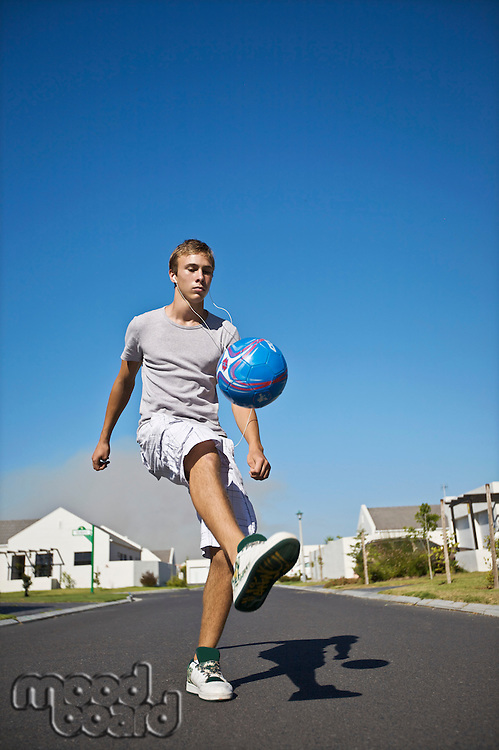 South Africa Cape Town teenage boy kicking ball on street