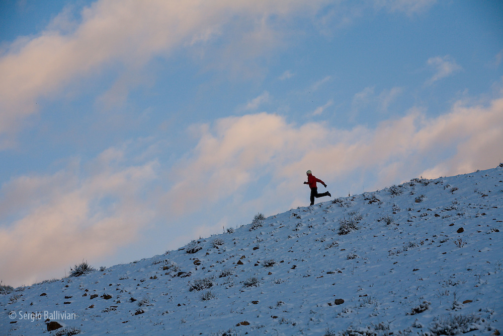 Mid-adult man running across a snowy field in the Front Range of Boulder, CO