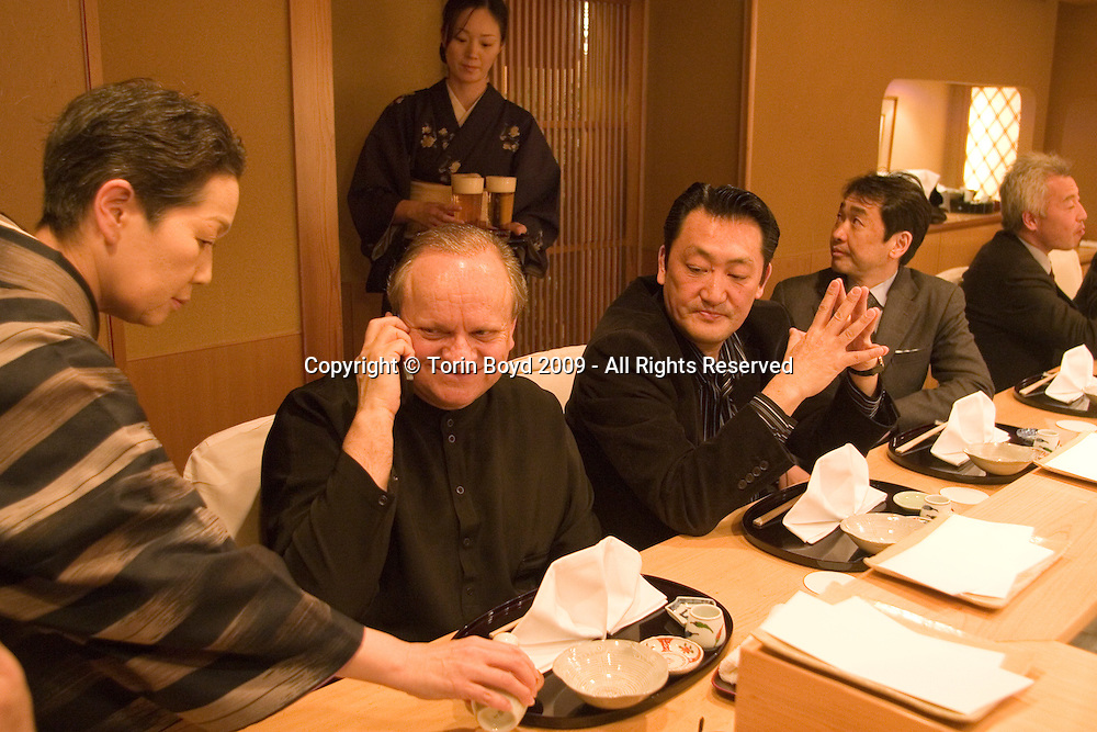 "This is world renowned chef Joel Robuchon shortly after arriving Tokyo on February 6, 2009. Here is seen here having dinner at a high end Japanese tempura restaurant called Tempura Tensei which is listed with one star in the Japanese Michelin Guide. The kimono woman is pouring him sake. The two Japanese men next to him are Mitsugu Yasuda (1st on his left) who's closely assisting Robuchon during his stay in Japan, and Ken Matsui (2nd on his left), Senior Managing Director of Four Seeds Corporation his is Robuchon's partner company in Japan. Robuchon traveled from his home base in Paris via Air France to attend an international food exposition called ""2009 Tokyo Taste"". This three day event from February 9-11, 2009 showcases some of the world's most famous chefs including Robuchon and Ferran Adria (of El Bulli) who are both Honorary Advisors to this event. Other chefs participating in this event are Heston Blumenthal, Pierre Gagnaire, Jacques Puisais, Bruno Menard, Herve This, Ferran Adria, and Nobuyuki Matsuhisa to name a few. Robuchon also has restaurants in Tokyo and Nagoya Japan including; L'Atelier de Joel Robuchon and the prestigious Le Chateau de Joel Robuchon. These establishments are connected with Four Seeds Corporation, a Japanese corporation that owns and operates several popular restaurant chains around Japan."