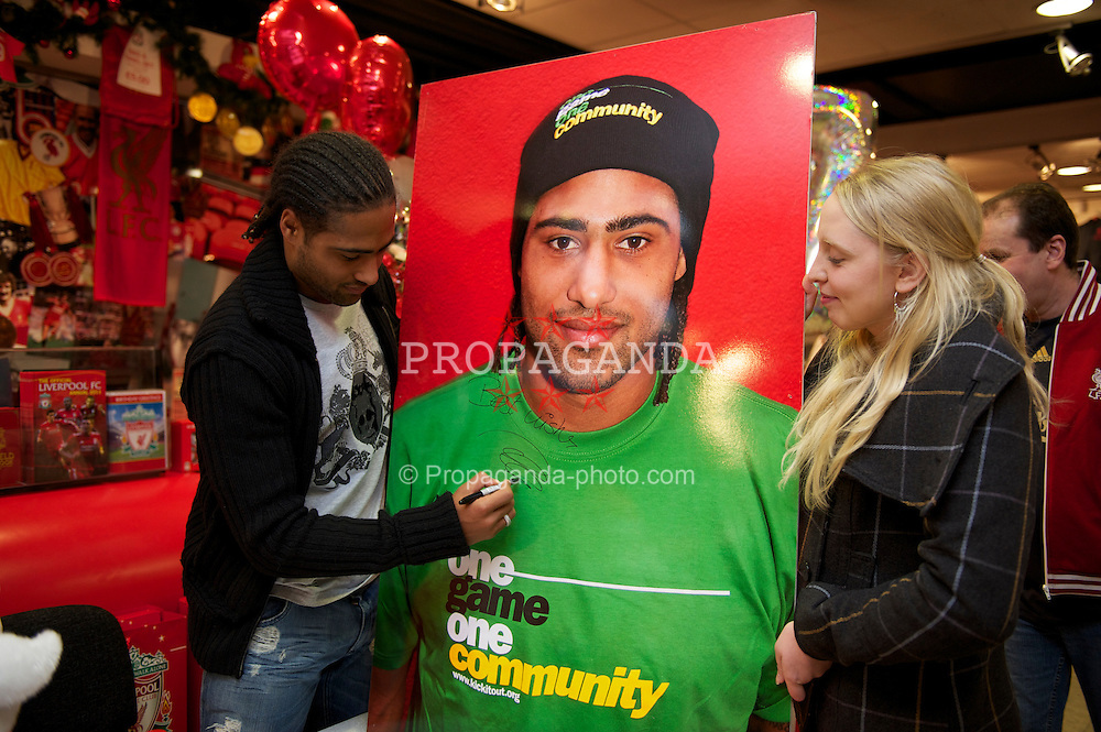 LIVERPOOL, ENGLAND - Friday, November 26, 2010: Liverpool's Glen Johnson signs a giant photo of himself for a supporter during a signing session for supporters at the Liverpool FC Club Shop at Anfield. (Photo by David Rawcliffe/Propaganda)