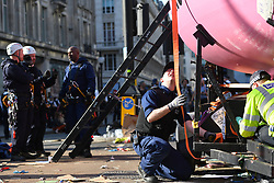 © Licensed to London News Pictures. 19/04/2019. London, UK.  A pink boat that has blocked Oxford Circus since Monday as part of the Extinction Rebellion protests is removed by police as demonstrators cheer on. Photo credit: Guilhem Baker/LNP