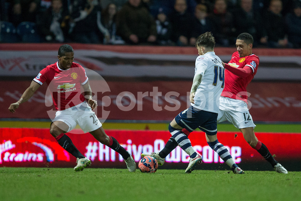 Manchester United's Chris Smalling and Antonio Valencia attempt to tackle Preston North End's Joe Garner during the The FA Cup match between Preston North End and Manchester United at Deepdale, Preston, England on 16 February 2015. Photo by James Williamson.