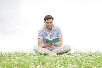 Young man reading book while sitting on grass against sky